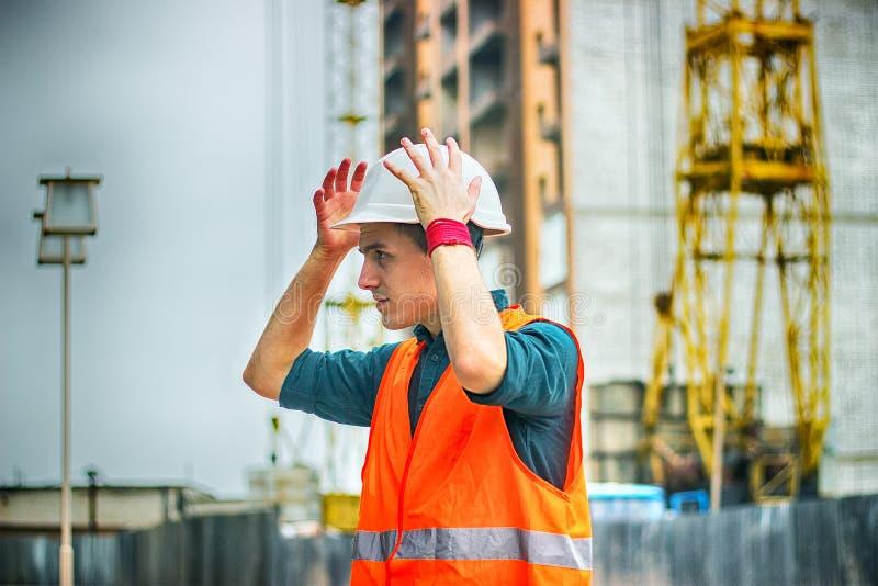 Ingeniero o arquitecto que comprueba el casco de seguridad del equipo protector personal en el emplazamiento de la obra imagen de archivo