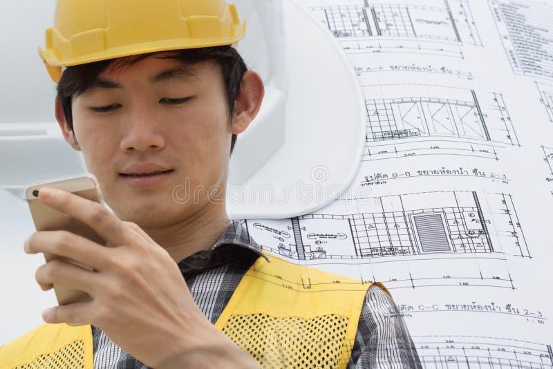 Ingeniero o capataz de la exposición doble que usa el teléfono elegante en su trabajo con en el emplazamiento de la obra fotografía de archivo