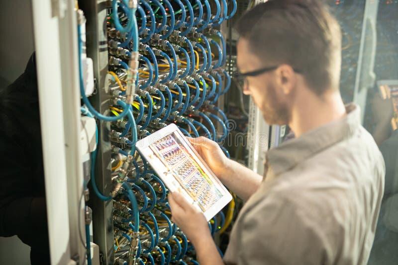 Ingeniero ocupado del servidor que analiza conexiones imagen de archivo libre de regalías