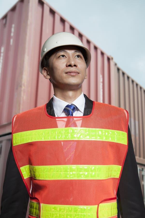 Ingeniero orgulloso en el workwear protector que se coloca en una yarda de envío imágenes de archivo libres de regalías