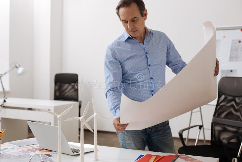 Ingeniero profesional que es implicado en el proyecto de las turbinas de viento del edificio fotos de archivo