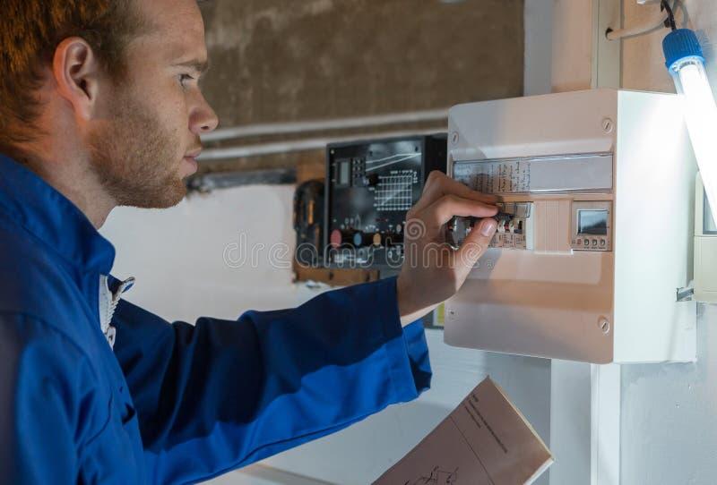 Ingeniero que ajusta el termóstato del sistema de calefacción foto de archivo libre de regalías