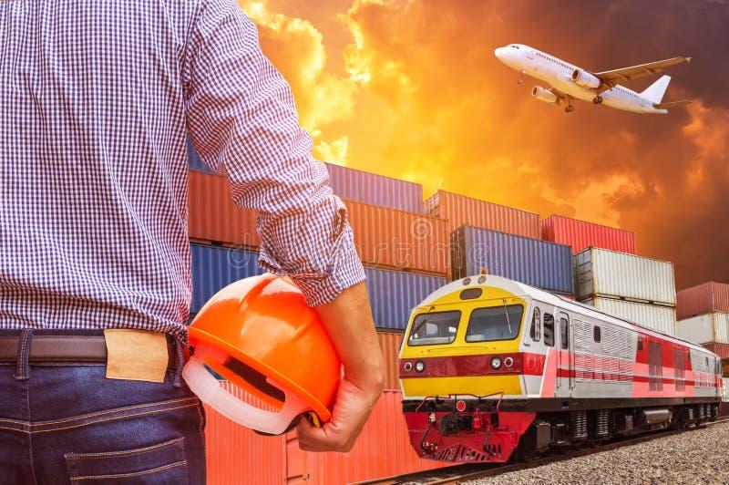 Ingeniero que celebra el tren de carga comercial de trabajo amarillo del cargo del control del casco de seguridad con la pila del foto de archivo libre de regalías