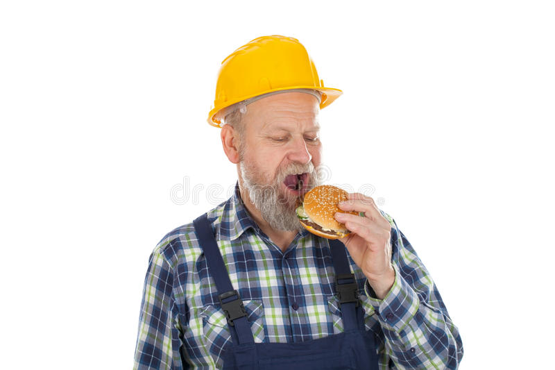 Ingeniero que come la hamburguesa imagen de archivo libre de regalías