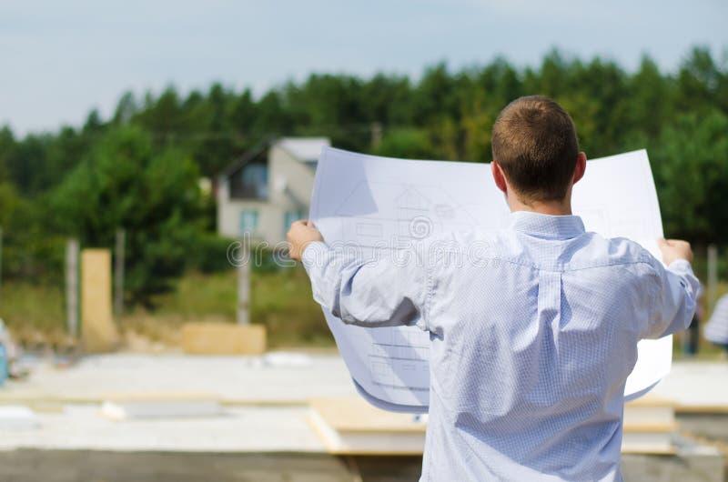 Ingeniero que comprueba un plan del edificio en sitio imagenes de archivo