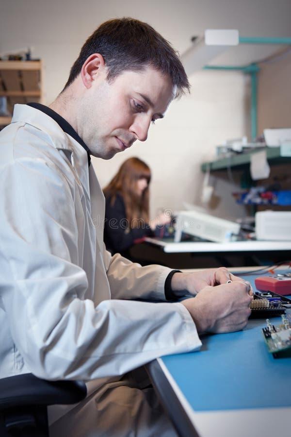 Ingeniero que prueba un ensamblaje de la tarjeta de circuitos foto de archivo