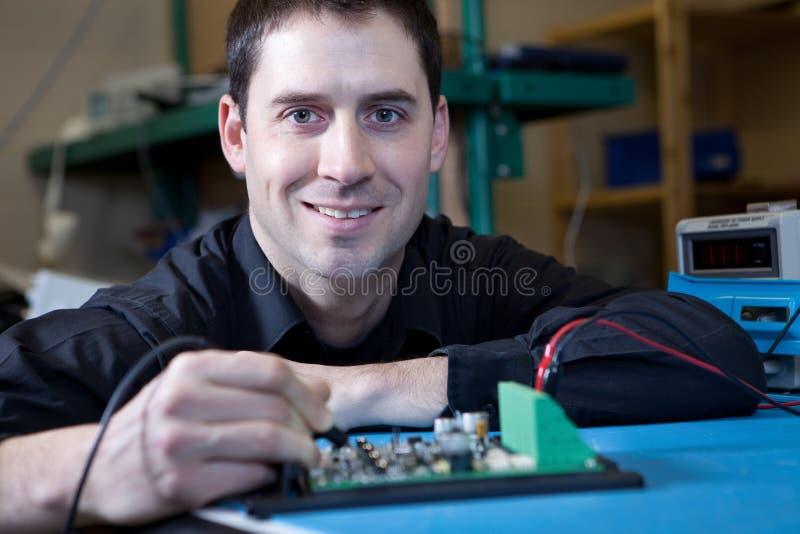 Ingeniero que prueba un ensamblaje de la tarjeta de circuitos imágenes de archivo libres de regalías