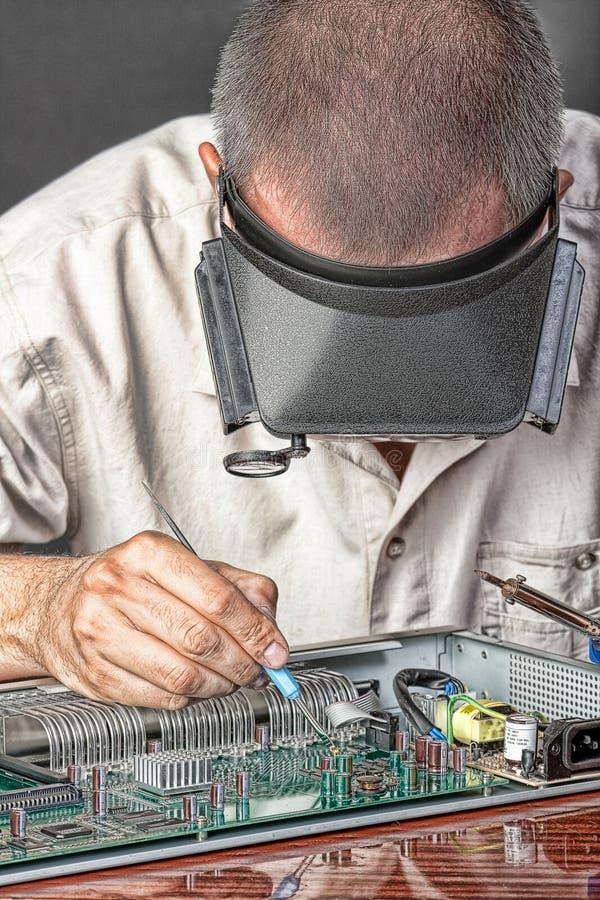 Ingeniero que repara la tarjeta de circuitos fotos de archivo