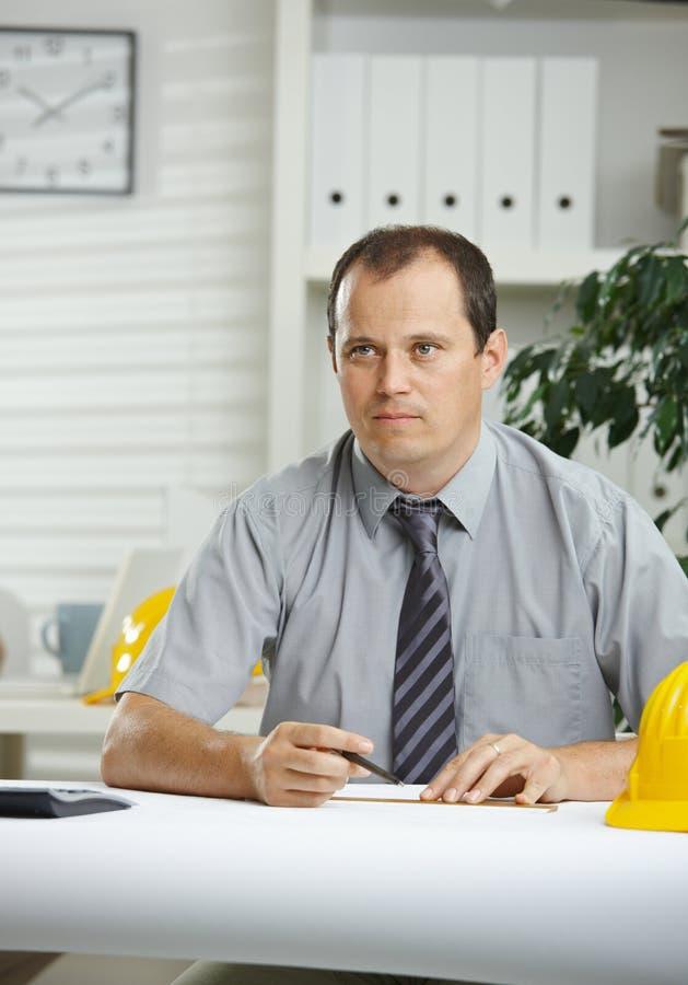 Ingeniero que trabaja en el escritorio foto de archivo