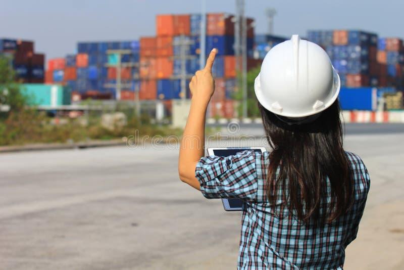 Ingeniero que trabaja en el fondo delantero del envase y de las importaciones/exportaciones, transporte del negocio del concepto  fotografía de archivo