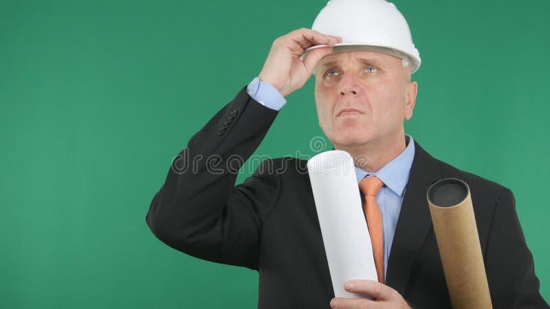 Ingeniero serio Keep su casco con la mano y la mirada para arriba imagenes de archivo