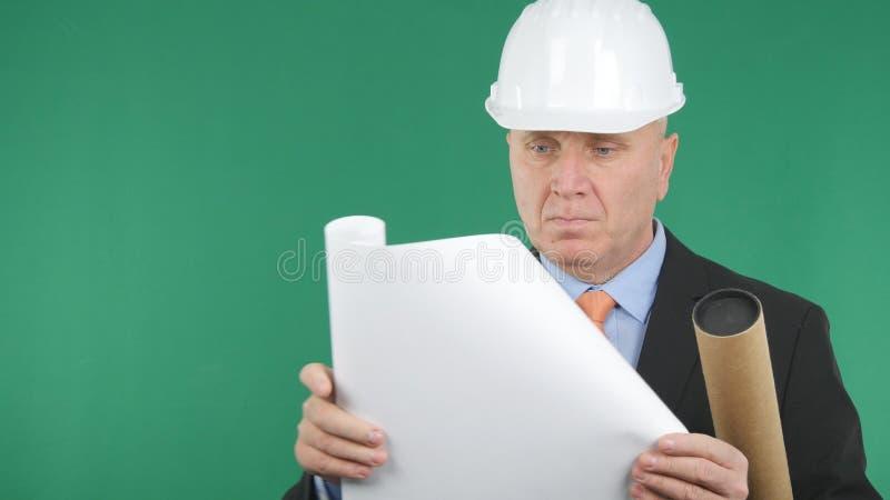 Ingeniero serio Opening y lectura de un proyecto técnico imagen de archivo
