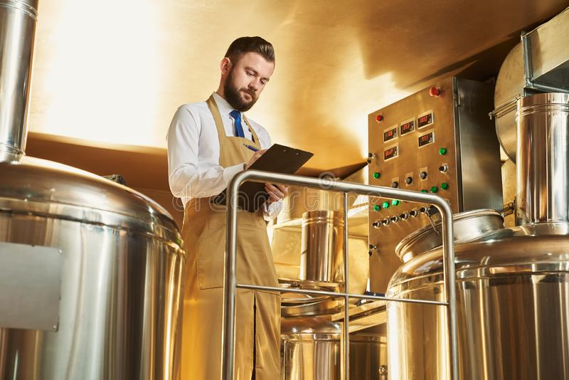 Ingeniero serio que examina proceso de la cervecería fotos de archivo