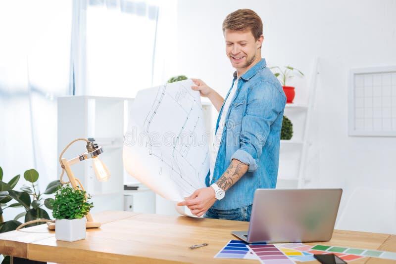 Ingeniero sonriente que mira el ordenador portátil y sostener un dibujo imagen de archivo