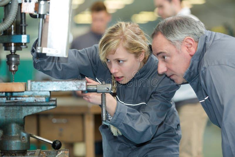 Ingeniero Training Female Apprentice en la fresadora fotos de archivo libres de regalías