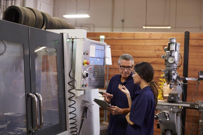 Ingeniero Training Female Apprentice en la máquina del CNC fotos de archivo