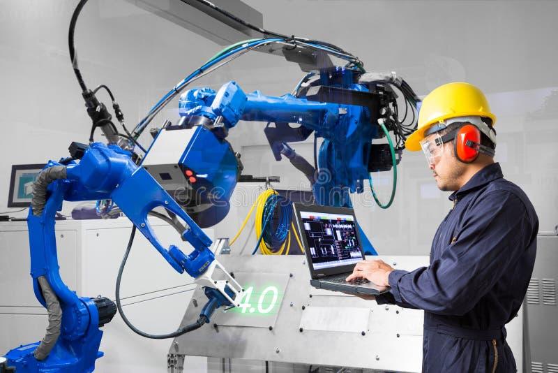 Ingeniero usando el corte robótico del laser del control de ordenador portátil en la placa de metal, industria 4 La palabra del c imagenes de archivo