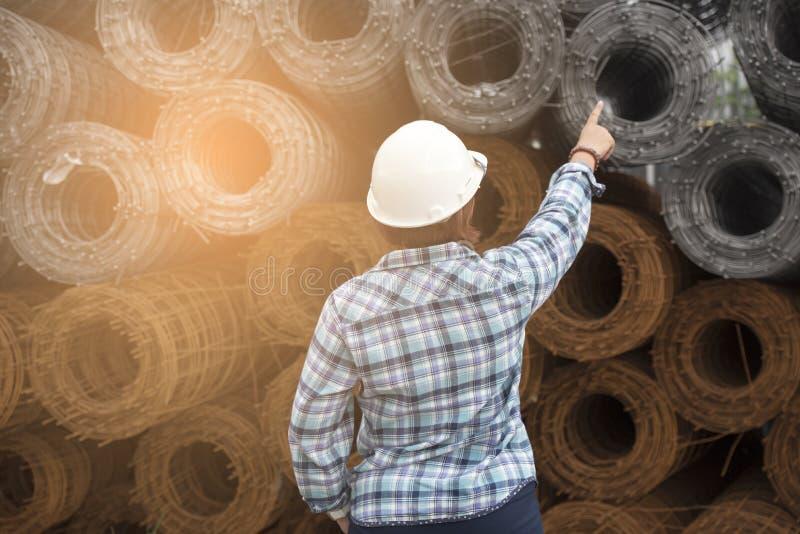 Ingeniero Wear Blue Shirt de la mujer y casco blanco en un industrial fotos de archivo
