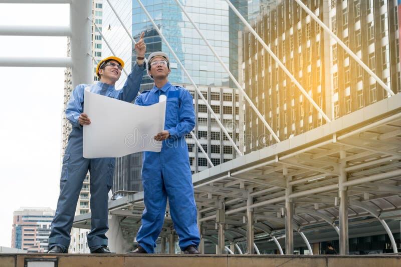 Ingeniero y arquitecto que trabajan en el emplazamiento de la obra imagen de archivo