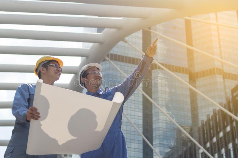 Ingeniero y arquitecto que trabajan en el emplazamiento de la obra con bluepri fotos de archivo
