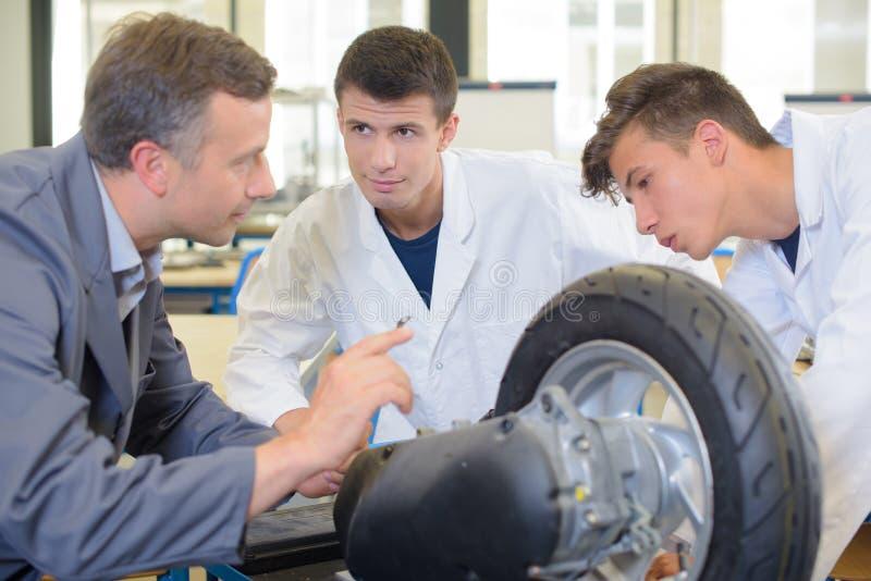 Ingeniero y estudiantes que miran la rueda imágenes de archivo libres de regalías