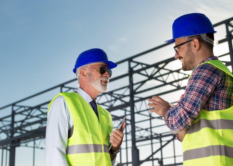 Ingeniero y trabajador de construcción en el solar imagen de archivo