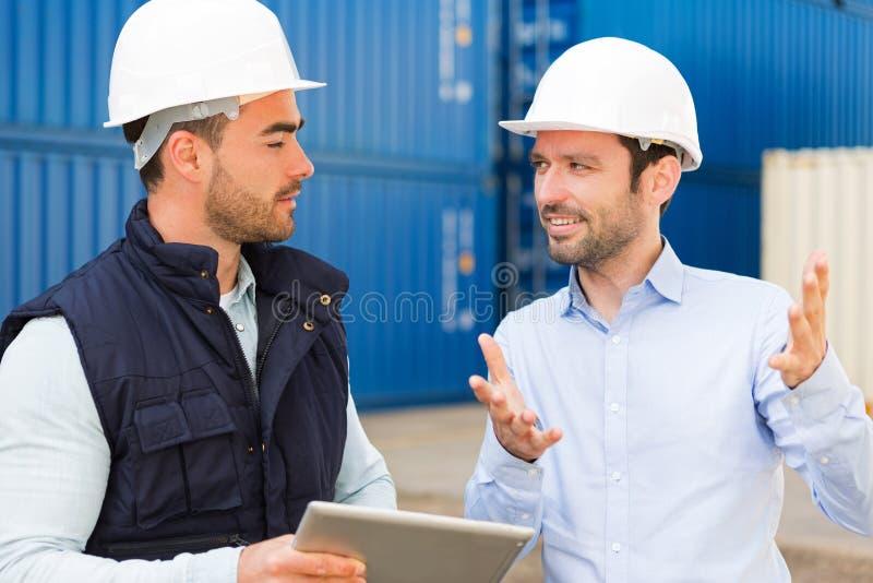 Ingeniero y trabajador que hablan sobre trabajo sobre el muelle imagenes de archivo