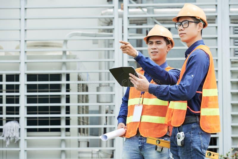 Ingenieros asiáticos con la tableta que mira distancia foto de archivo libre de regalías
