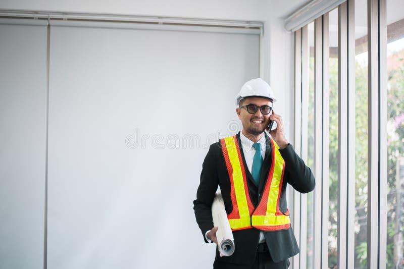 Ingenieros asiáticos del hombre usando modelo del teléfono móvil y el sostenerse en oficina fotos de archivo