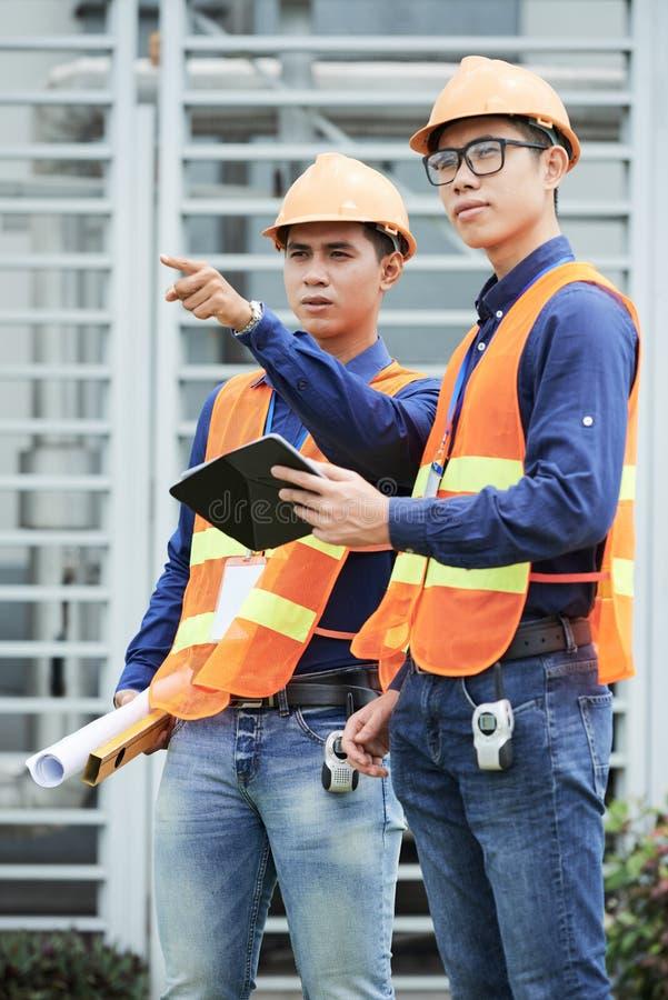Ingenieros asiáticos que miran distancia en emplazamiento de la obra foto de archivo libre de regalías