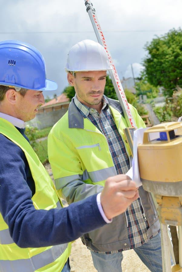 Ingenieros civiles con el teodolito imagen de archivo