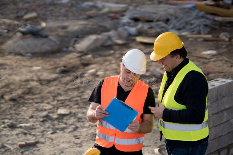 Ingenieros civiles en el trabajo sobre emplazamiento de la obra imagenes de archivo
