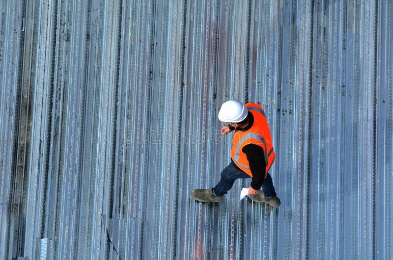 Ingenieros civiles que examinan el progreso de trabajo del tejado del metal fotografía de archivo