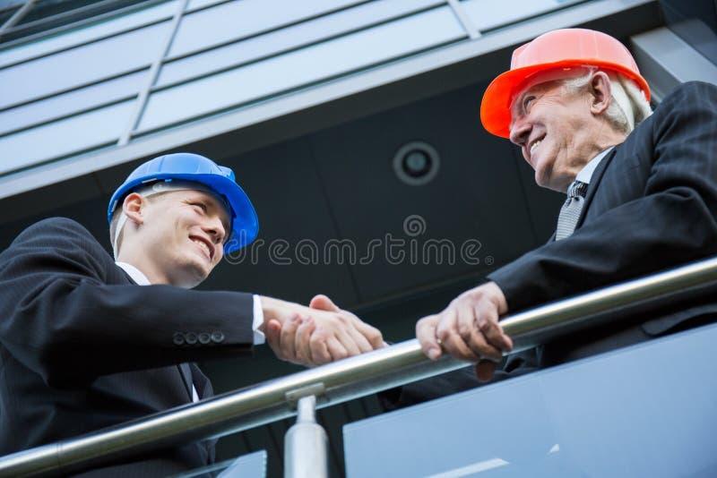 Ingenieros civiles que sacuden las manos imagen de archivo