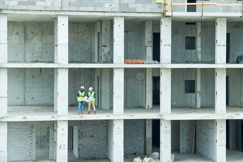 Ingenieros de construcción en el edificio inacabado fotografía de archivo libre de regalías