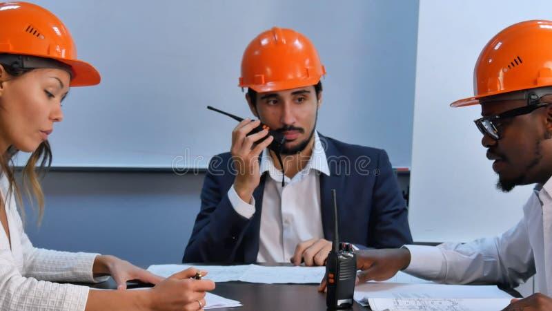 Ingenieros de construcción multirraciales en la reunión en oficina moderna brillante fotografía de archivo libre de regalías