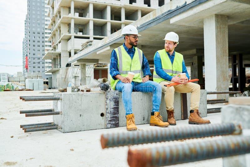 Ingenieros de construcción que charlan durante rotura fotografía de archivo