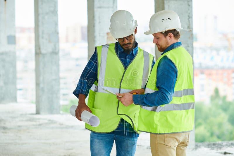 Ingenieros de construcción que estudian proyecto sobre la tableta imagenes de archivo