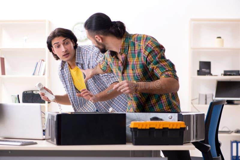 Ingenieros de las TIC que trabajan en problema del hardware fotos de archivo libres de regalías