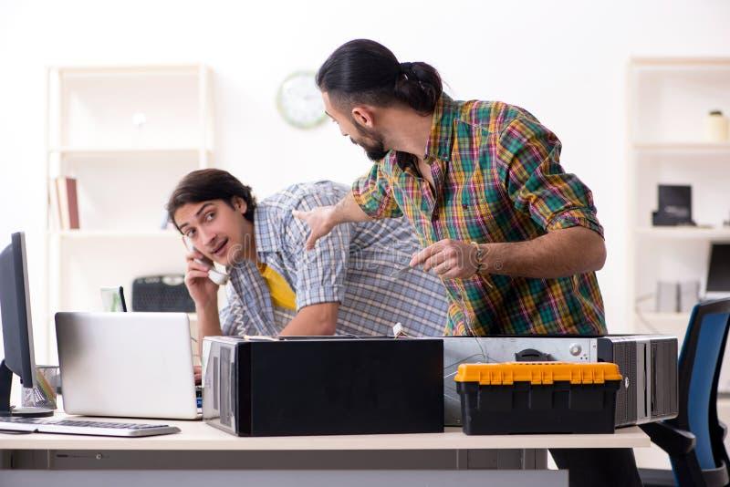 Ingenieros de las TIC que trabajan en problema del hardware foto de archivo libre de regalías