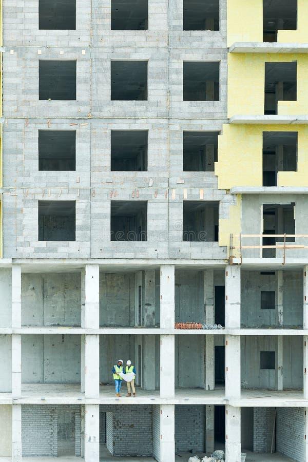 Ingenieros en el edificio bajo construcción fotos de archivo