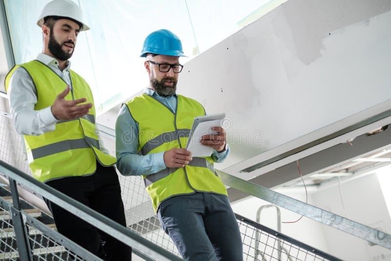 Ingenieros en los cascos de protecci?n que tienen conversaci?n foto de archivo libre de regalías
