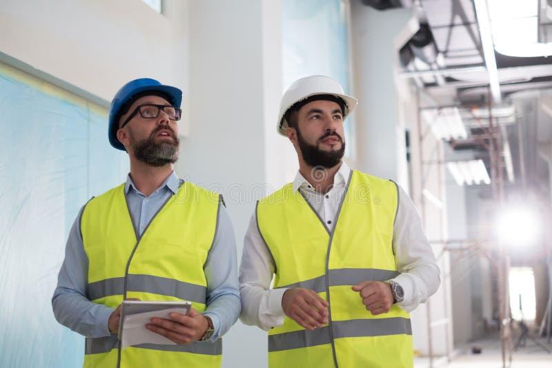 Ingenieros en los cascos de protecci?n que tienen conversaci?n imágenes de archivo libres de regalías