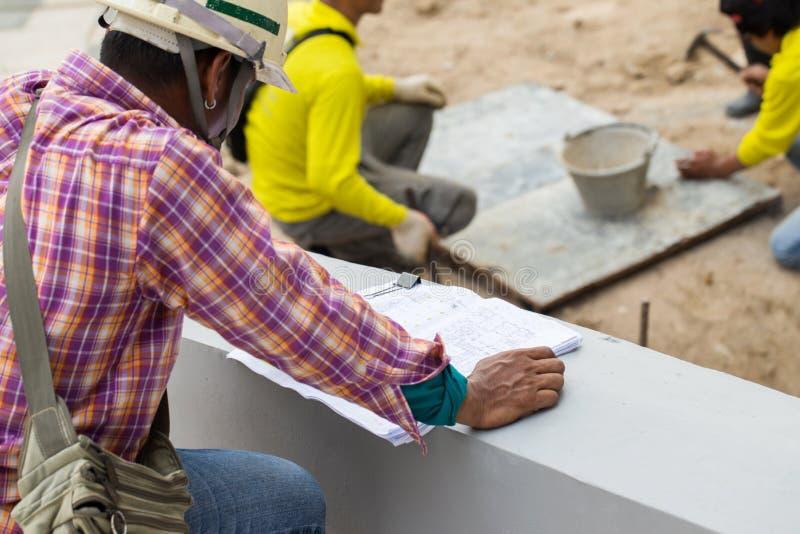Ingenieros en solar que comprueban planes Ingeniero o arquitecto del plan del edificio para la construcción en el sitio del traba foto de archivo libre de regalías
