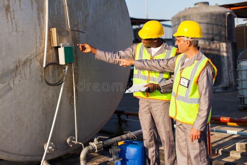 Ingenieros industriales que examinan fotos de archivo
