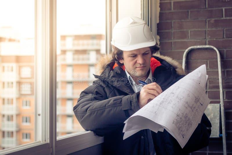 Ingenieros jovenes que usan el punto de pluma al papel de modelo para examinar la estructura de la casa antes de presentarla en foto de archivo libre de regalías