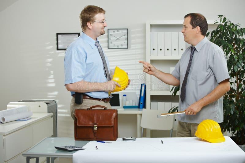 Ingenieros que hablan en la oficina imagenes de archivo