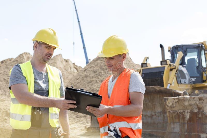Ingenieros que leen el tablero en el emplazamiento de la obra contra el cielo claro imágenes de archivo libres de regalías