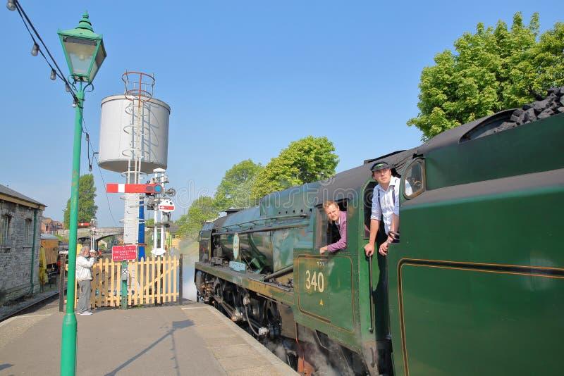 Ingenieros que supervisan la entrada de un tren del vapor en el ferrocarril de Swanage fotografía de archivo libre de regalías