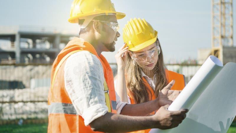 Ingenieros y arquitectos del emplazamiento de la obra con el casco de seguridad con el fondo constructivo con el plan o el modelo imágenes de archivo libres de regalías